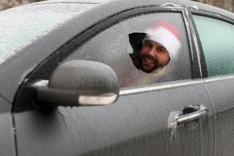Homem em um tampão vermelho de Santa Claus em um carro com vidro quebrado imagem de stock