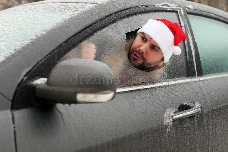 Homem em um tampão vermelho de Santa Claus em um carro com vidro quebrado imagens de stock