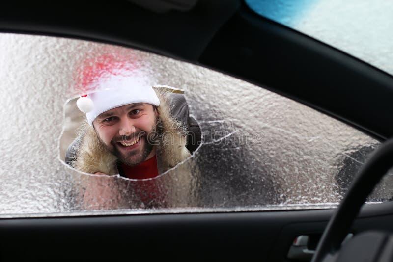 Homem em um tampão vermelho de Santa Claus em um carro com vidro quebrado fotografia de stock