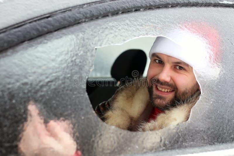 Homem em um tampão vermelho de Santa Claus em um carro com vidro quebrado fotos de stock royalty free