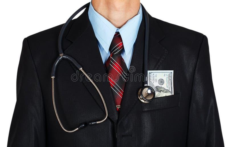 Homem em um terno de negócio com um estetoscópio e um dinheiro no bolso foto de stock