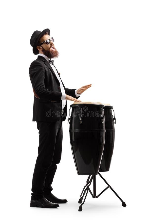 Homem em um terno preto que joga cilindros do conga fotos de stock royalty free