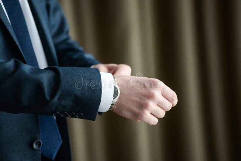 Homem em um tux que fixa seu botão de punho imagens de stock royalty free