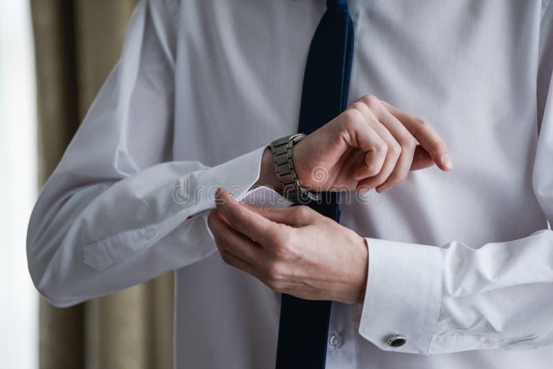Homem em um tux que fixa seu botão de punho foto de stock