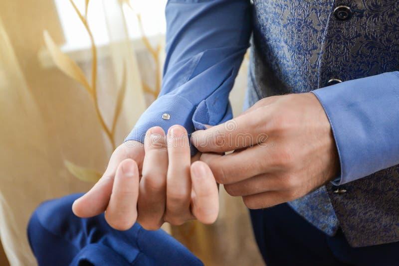 Homem em um tux que fixa seu botão de punho fotos de stock royalty free