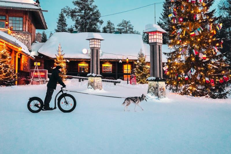 Homem em uma bicicleta e em um cão de puxar trenós de montada em Santa Claus Village em Rovaniemi em Lapland em Finlandia imagens de stock royalty free