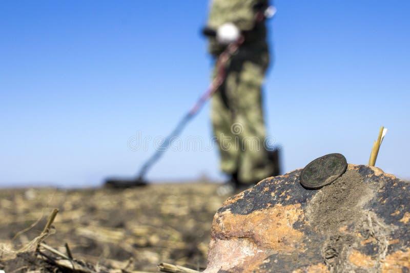 Homem em uma caça ao tesouro com um detector de metais nas madeiras no campo foto de stock
