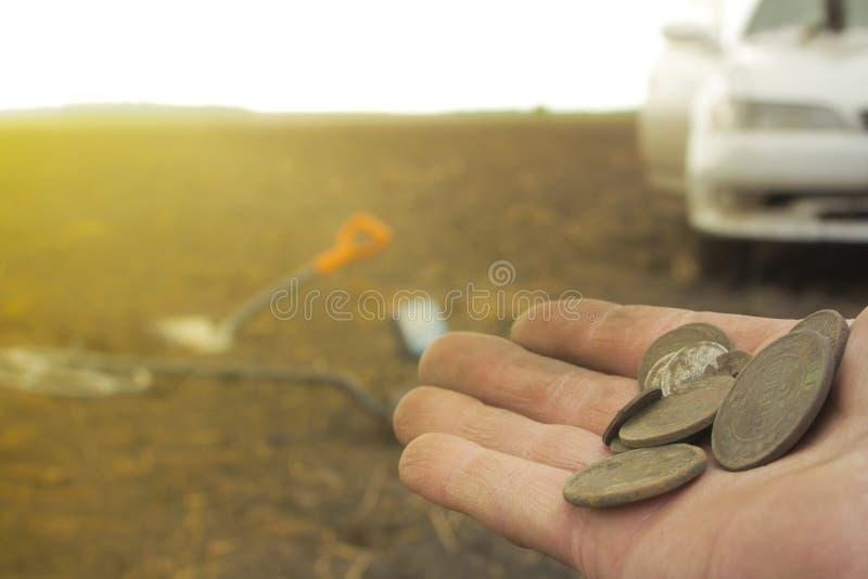 Homem em uma caça ao tesouro com um detector de metais nas madeiras no campo imagens de stock