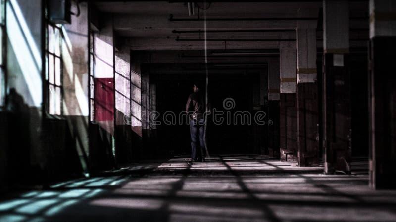 Homem em uma posição do revestimento em uma fábrica abandonada foto de stock