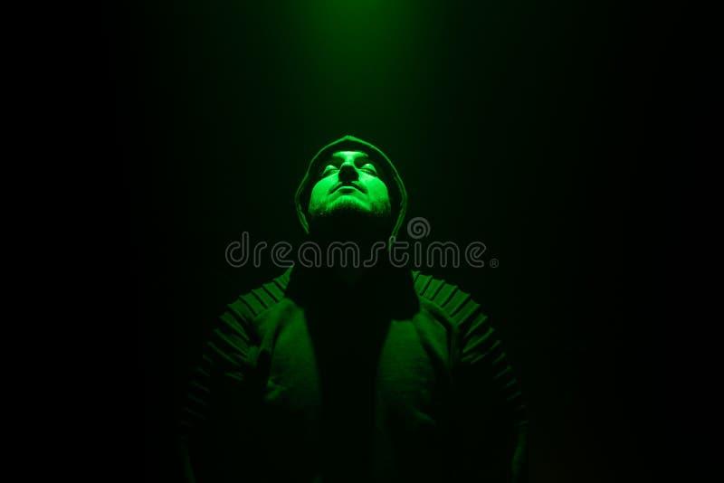 Homem em uma sala escura que olha acima a uma luz verde fotografia de stock