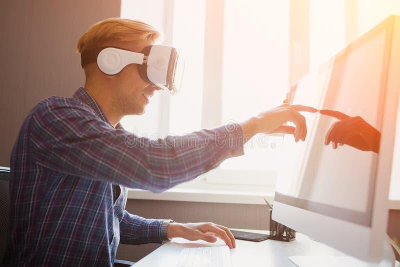 Homem em vidros de VR usando o computador fotografia de stock royalty free