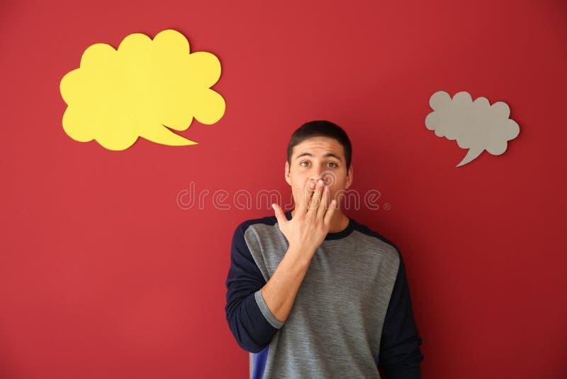 Homem emocional com bolhas do discurso no fundo da cor fotografia de stock royalty free
