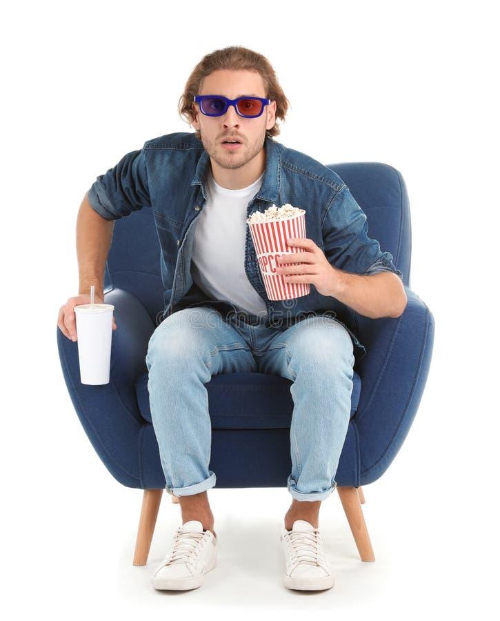 Homem emocional com os vidros 3D, a pipoca e a bebida sentando-se na poltrona durante a mostra do cinema imagem de stock royalty free