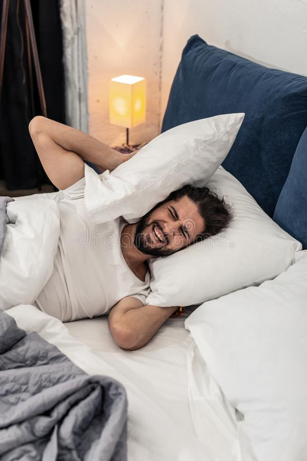 Homem emocional infeliz que quer continuar a dormir fotografia de stock