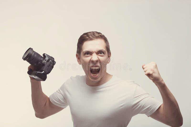 Homem emocional irritado com a câmera isolada no fundo claro Câmara digital da terra arrendada do homem novo e gritar Estilo de v foto de stock royalty free