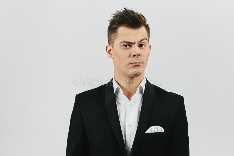 Homem emocional novo elegante e considerável na camisa branca e no terno preto à moda isolado no fundo branco fotos de stock royalty free