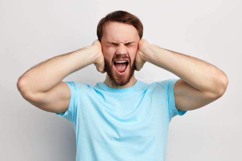 Homem emocional novo irritado irritado que obstrui as orelhas com mãos foto de stock