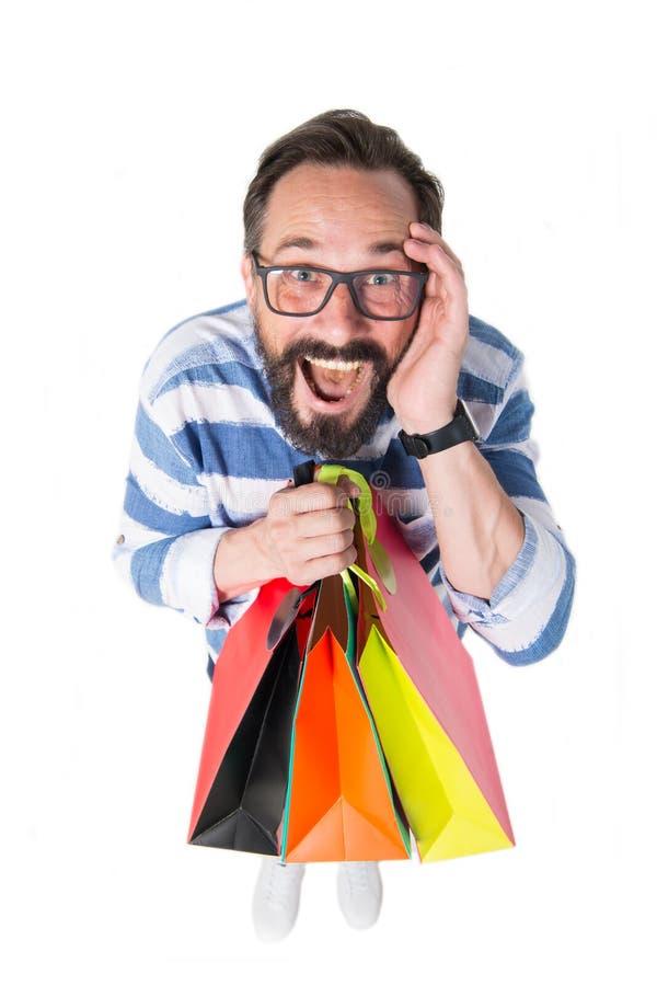 Homem emocional que guarda compras e que sente impresso por descontos imagem de stock royalty free