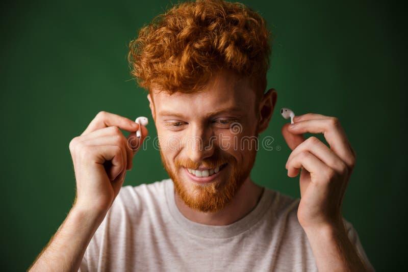 Homem encaracolado considerável do ruivo nos fones de ouvido brancos da inserção do t-shirt dentro fotos de stock