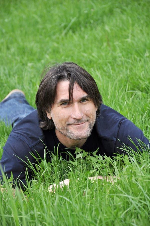 Homem, encontrando-se na grama verde fotos de stock
