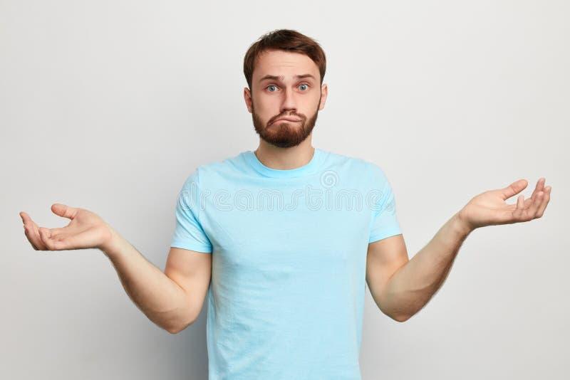 Homem engraçado confundido à nora que morde seus bordos fotografia de stock royalty free