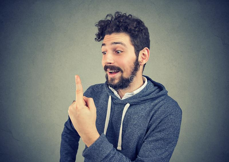 Homem engraçado entusiasmado que olha seu dedo fotografia de stock royalty free