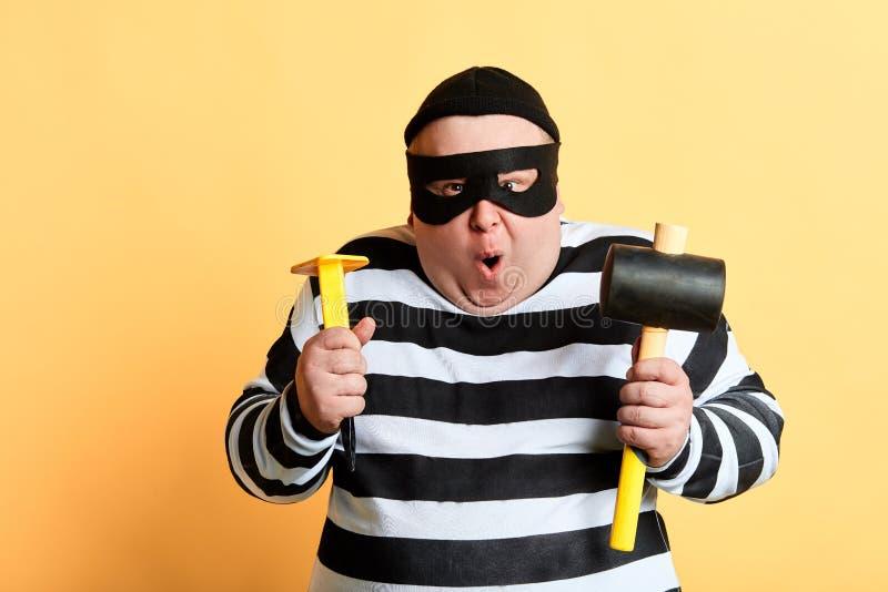 Homem engraçado excitado na máscara que está sendo excitada pelo dinheiro roubado imagens de stock