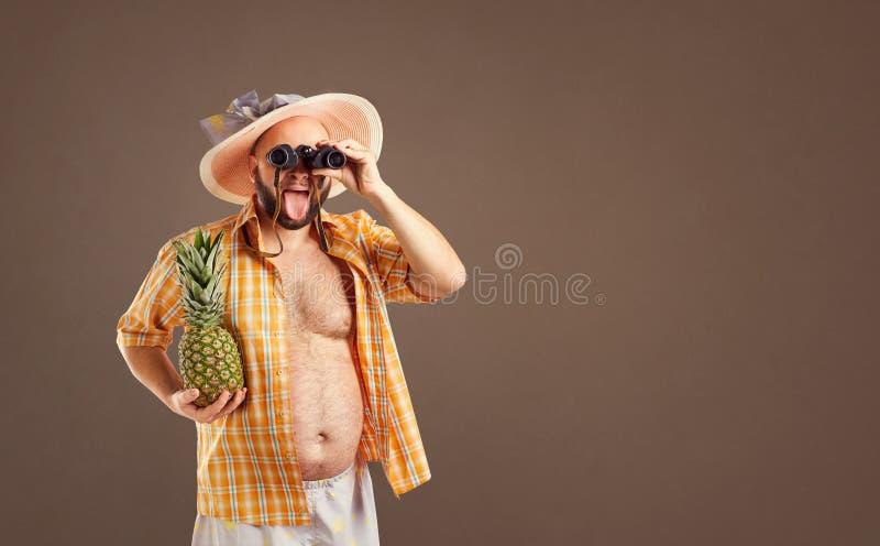 Homem engraçado grosso com uma barba em um chapéu com binóculos imagens de stock