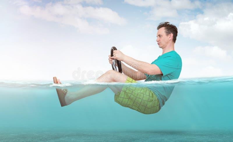 Homem engraçado no short, no t-shirt e nos passeios das sandálias no mar com um volante do carro Conceito de ir em f?rias imagens de stock