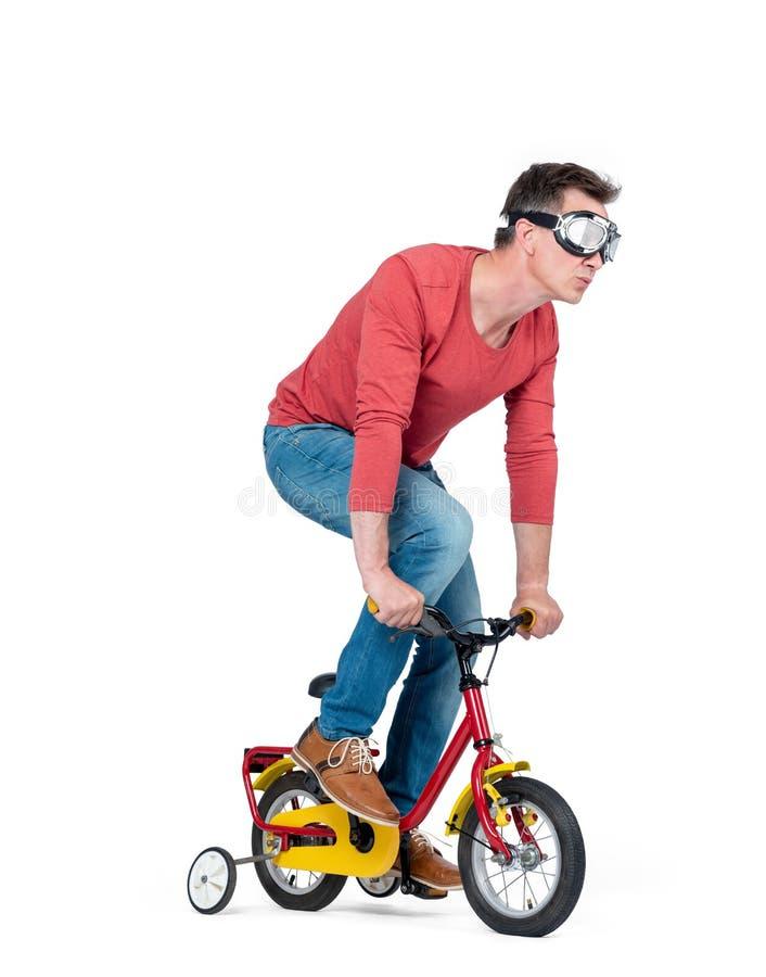 Homem engraçado nos óculos de proteção, calças de brim e uma bicicleta de umas crianças vermelhas do t-shirt pedais, isolada no f foto de stock royalty free