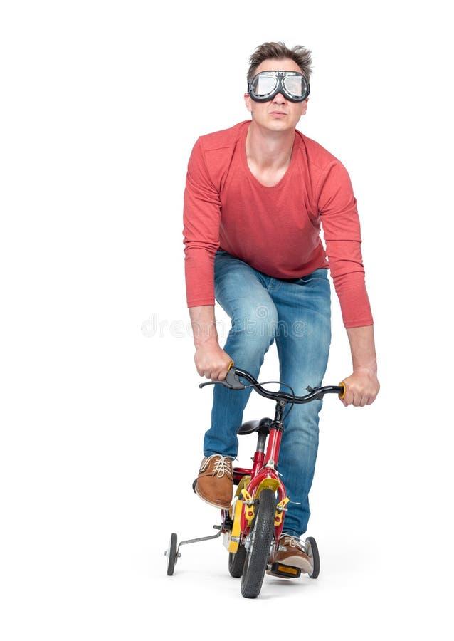 Homem engraçado nos óculos de proteção, calças de brim e uma bicicleta de umas crianças vermelhas do t-shirt pedais, isolada no f fotos de stock royalty free