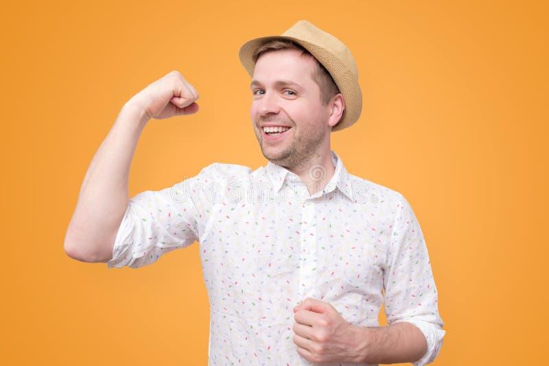 Homem engraçado novo do turista no bíceps das mostras do chapéu do verão fotos de stock