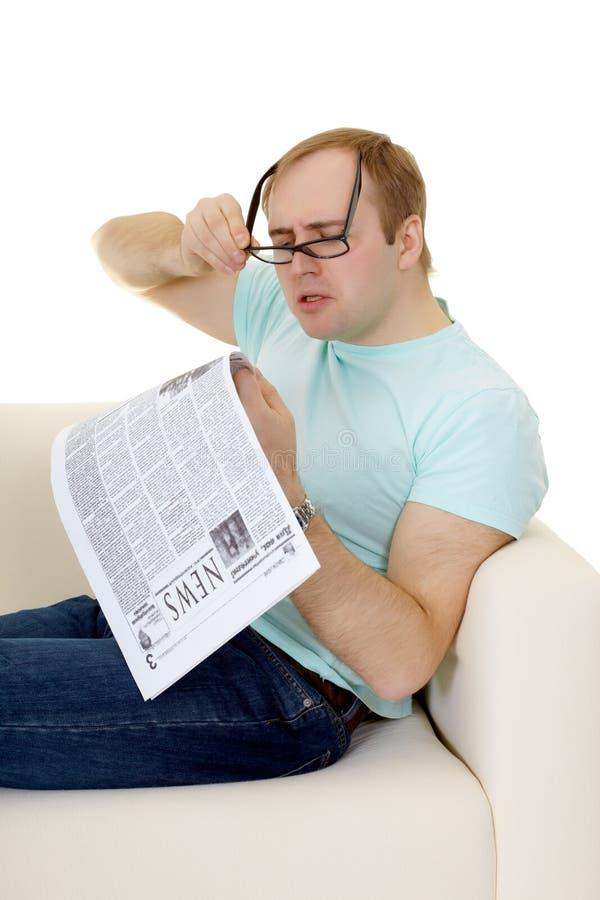 Homem engraçado que lê uma propaganda de trabalho no jornal foto de stock royalty free