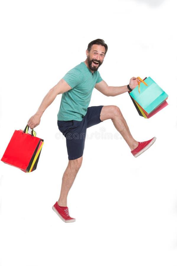 Homem engraçado que põe sua elevação do joelho ao correr com sacos de papel fotos de stock