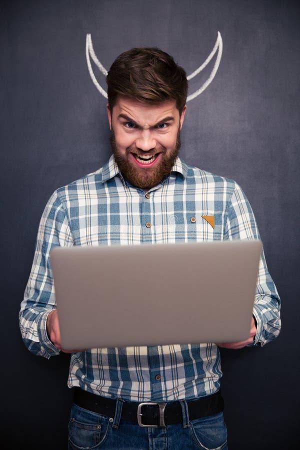 Homem engraçado que usa o portátil sobre o fundo do quadro-negro com chifres tirados imagem de stock royalty free