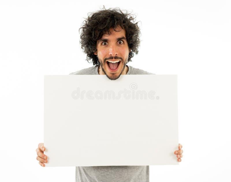Homem engra?ado novo que guarda a placa vazia para a propaganda Homens milenares que apontam no quadro de avisos branco fotos de stock royalty free