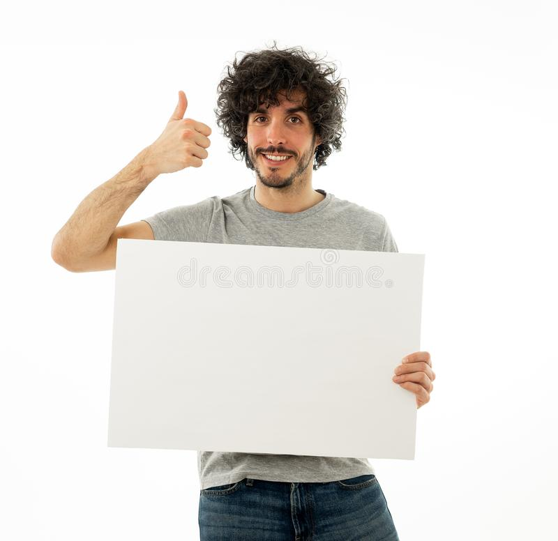 Homem engra?ado novo que guarda a placa vazia para a propaganda Homens milenares que apontam no quadro de avisos branco fotografia de stock