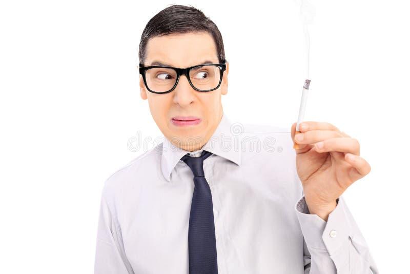 Homem enojado que guarda um cigarro fotos de stock