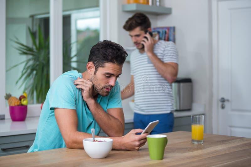 Homem enrijecido que usa o telefone na tabela fotografia de stock royalty free