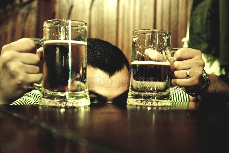Homem entre vidros de cerveja fotografia de stock