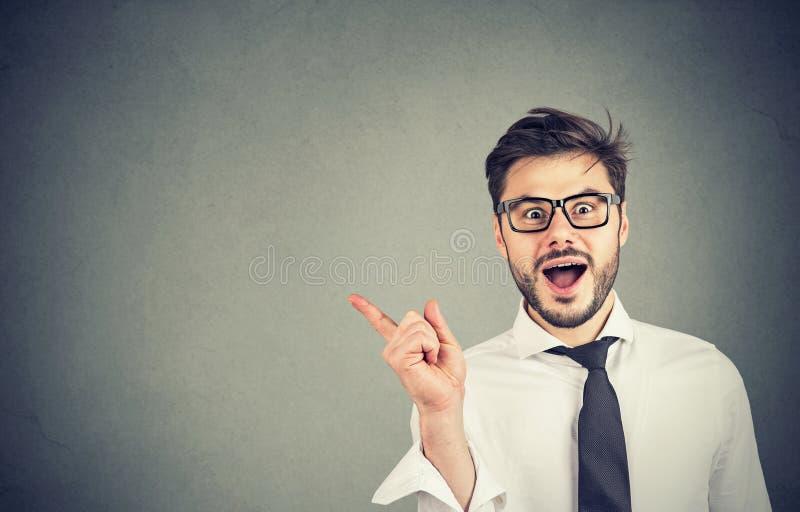 Homem entusiasmado que aponta afastado na propaganda fotos de stock