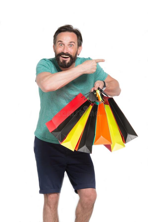 Homem entusiasmado que aponta ao shopping ao guardar compras fotos de stock