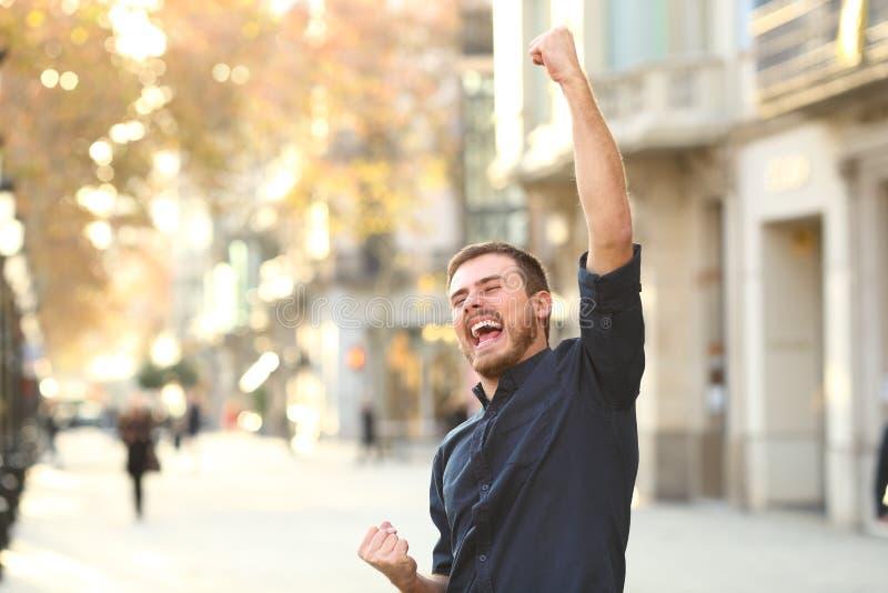 Homem entusiasmado que aumenta os braços que comemoram o sucesso fotografia de stock