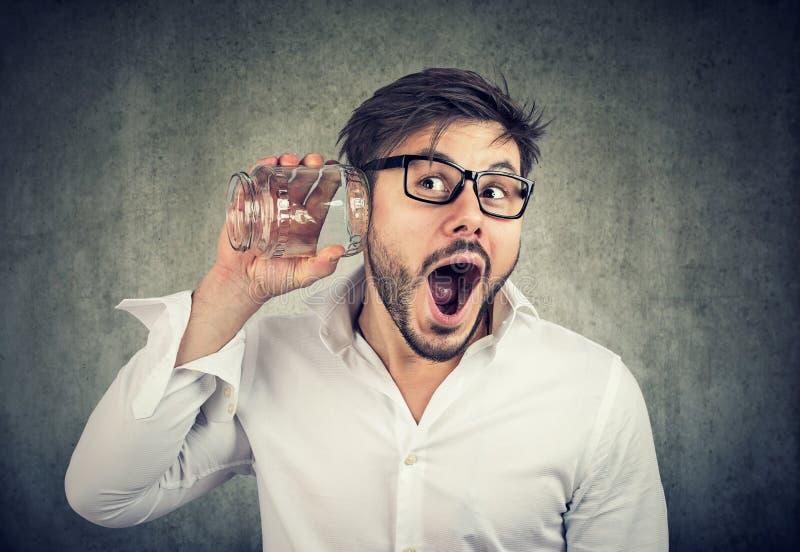 Homem entusiasmado que bisbilhota com frasco de vidro imagem de stock royalty free