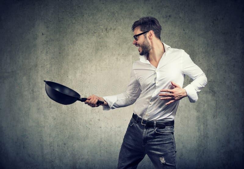 Homem entusiasmado que cozinha com frigideira imagens de stock