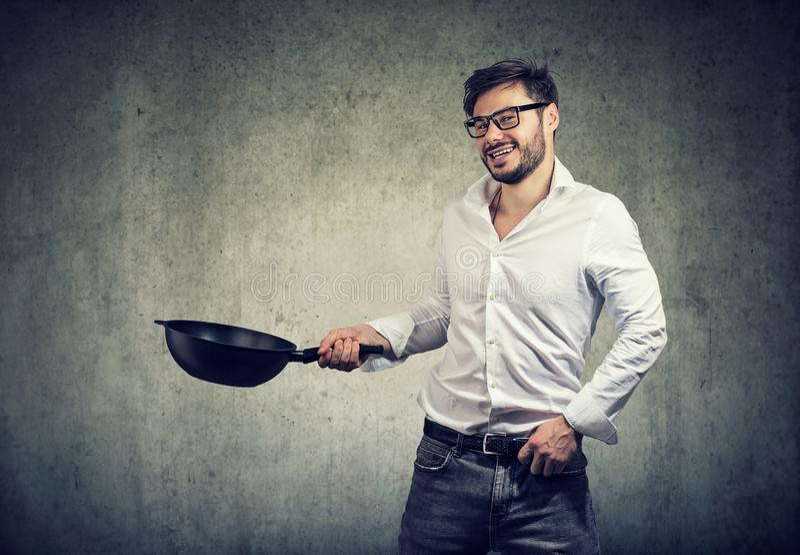 Homem entusiasmado que cozinha com frigideira imagem de stock