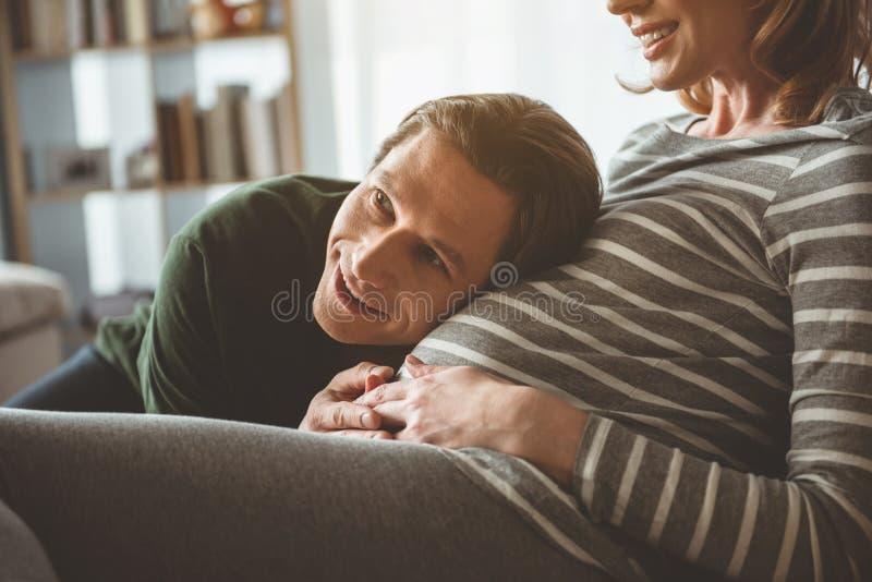 Homem entusiasmado que escuta seu nascituro através da barriga fêmea foto de stock royalty free