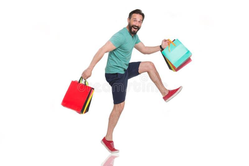Homem entusiasmado que faz etapas grandes ao levar suas compras maravilhosas fotos de stock
