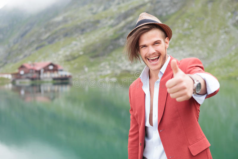 Homem entusiasmado que faz o gesto aprovado perto do lago foto de stock