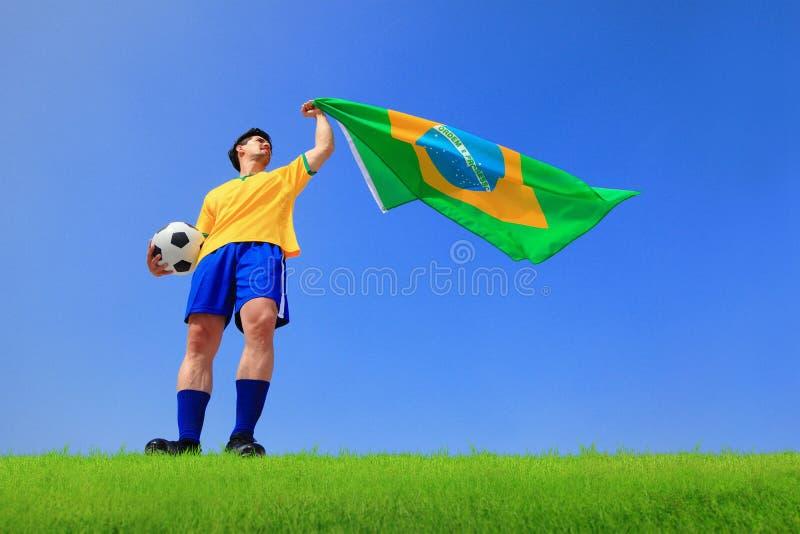 Homem entusiasmado que guarda uma bandeira de Brasil fotografia de stock royalty free
